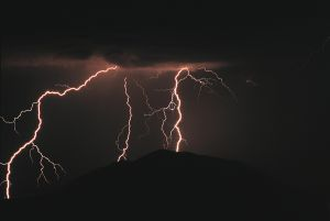 dark clouds release bright pink branching lightning bolts to the ground blow