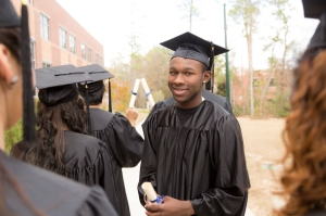 Education: Male graduate and friends on college campus.