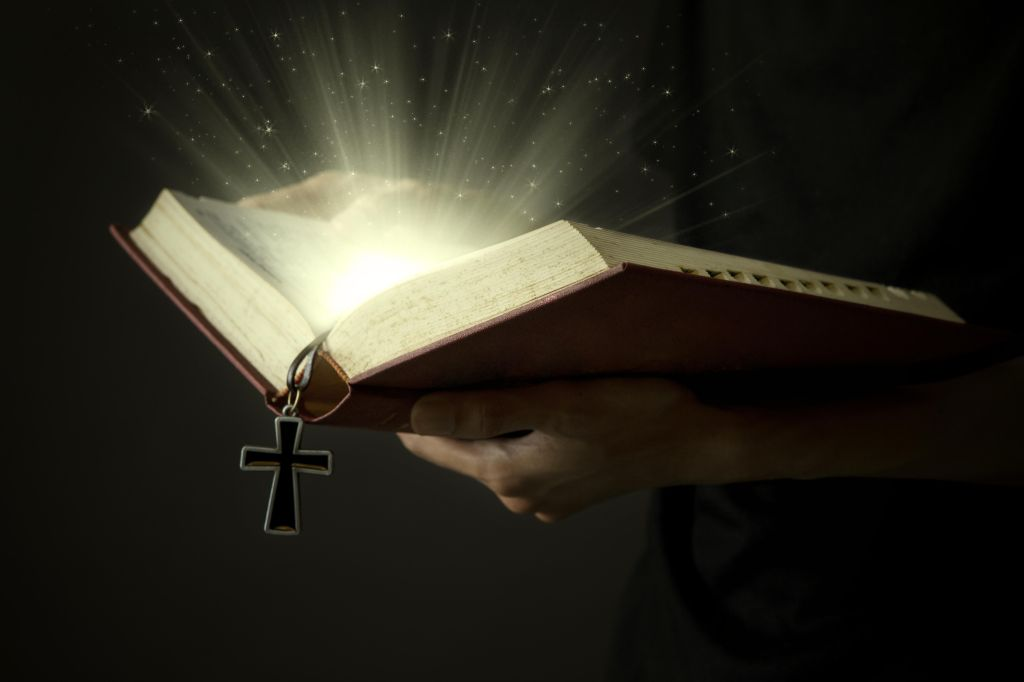 Hands of man holding holy bible and wooden rosary with magical rays