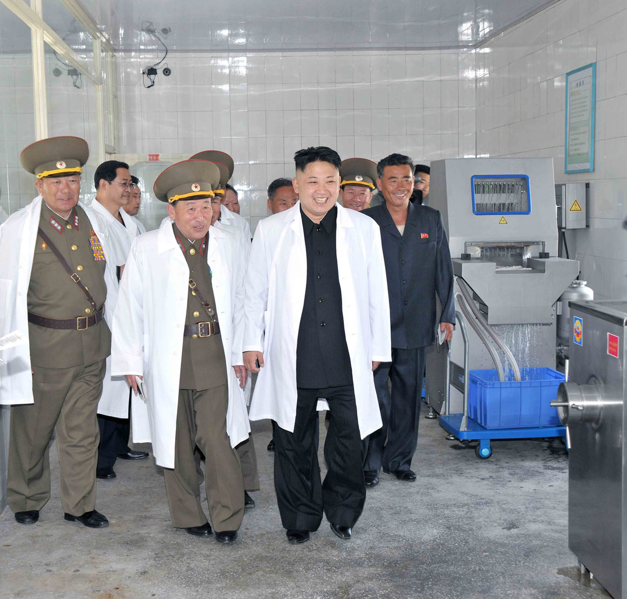 North Korean leader Kim Jong Un (C) inspecting a pig farm 2013
