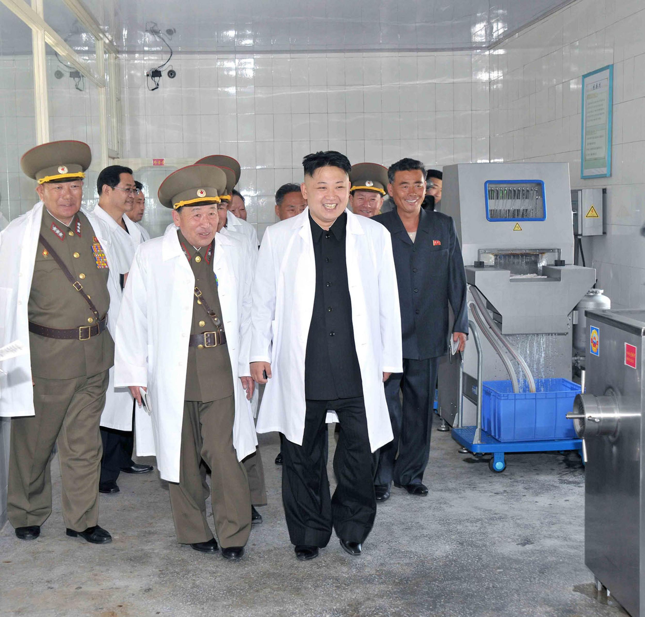 North Korean leader Kim Jong Un (C) inspecting a pig farm 2013