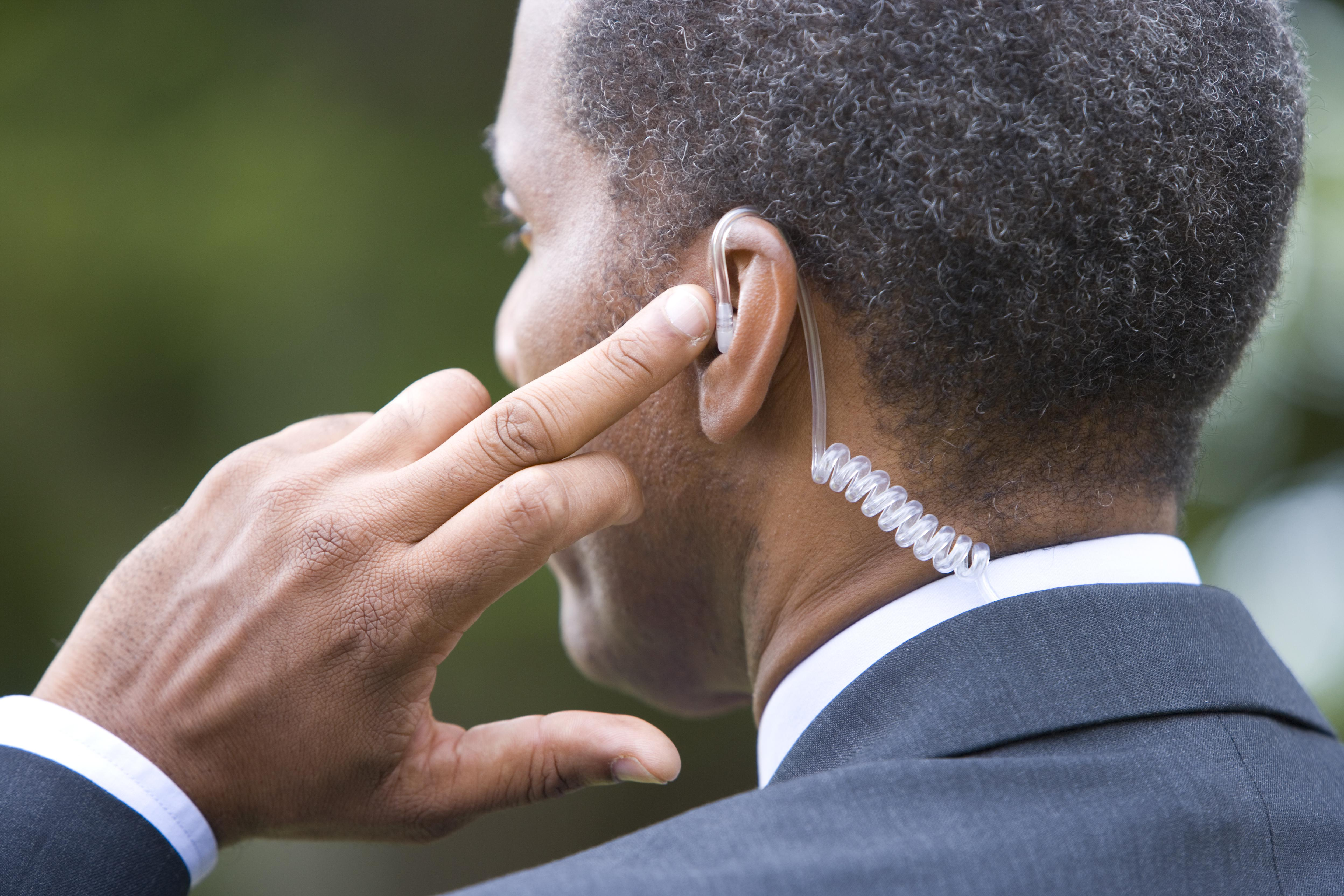 Man with finger on earpiece, rear view