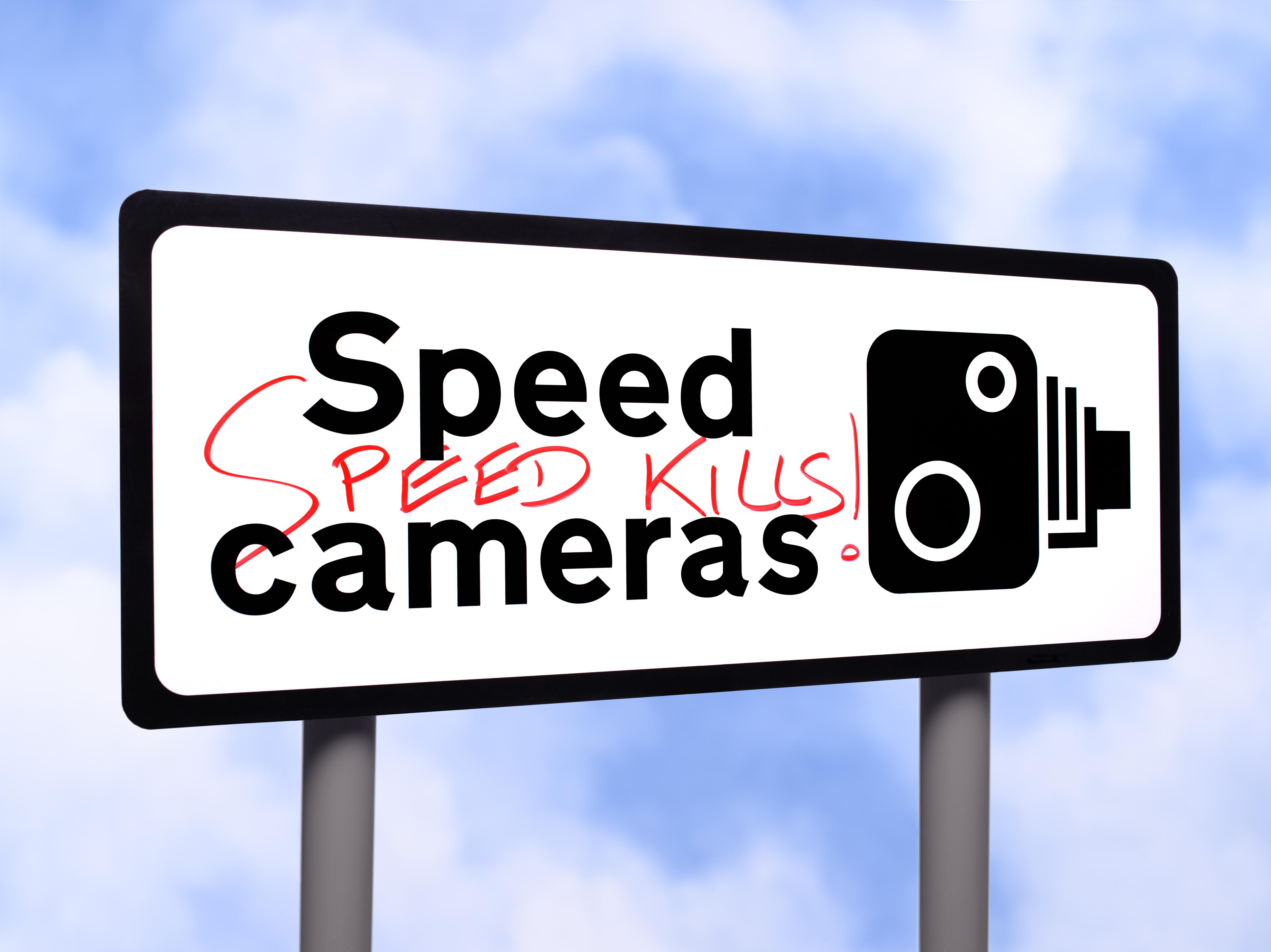 Speed camera sign with graffiti