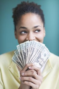 Young woman holding twenty dollar bills