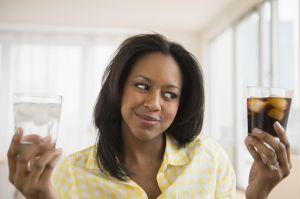 African American woman choosing water or soda