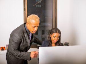 African American Woman & Man Staring At Computer